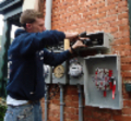 Electrician installing outdoor connections on multifamily house-859-229-641-564